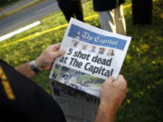 Steve Schuh, county executive of Anne Arundel County, holds a copy of The Capital Gazette near the scene of a shooting at the newspaper's office June 29 in Annapolis, Md. A man armed with smoke grenades and a shotgun attacked journalists in the building June 28 killing five people before police quickly stormed the building and arrested him, police and witnesses said.