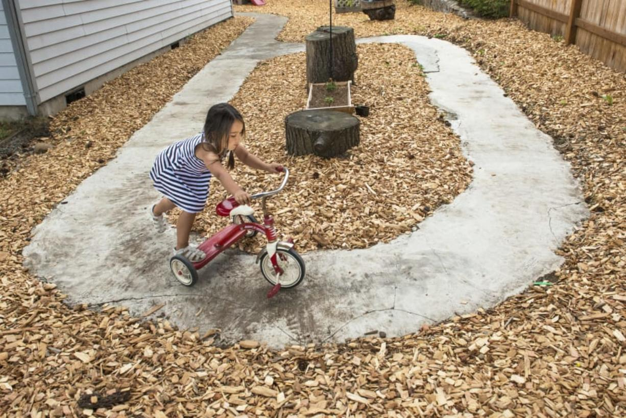 Four-year-old Lilyanne Obias of Vancouver pushes a tricycle during outdoor play at Tawney's Tots day care on a recent Monday. Helene Padget, who owns the day care, is among the many local in-home care providers who worry new state rules could hurt their industry.