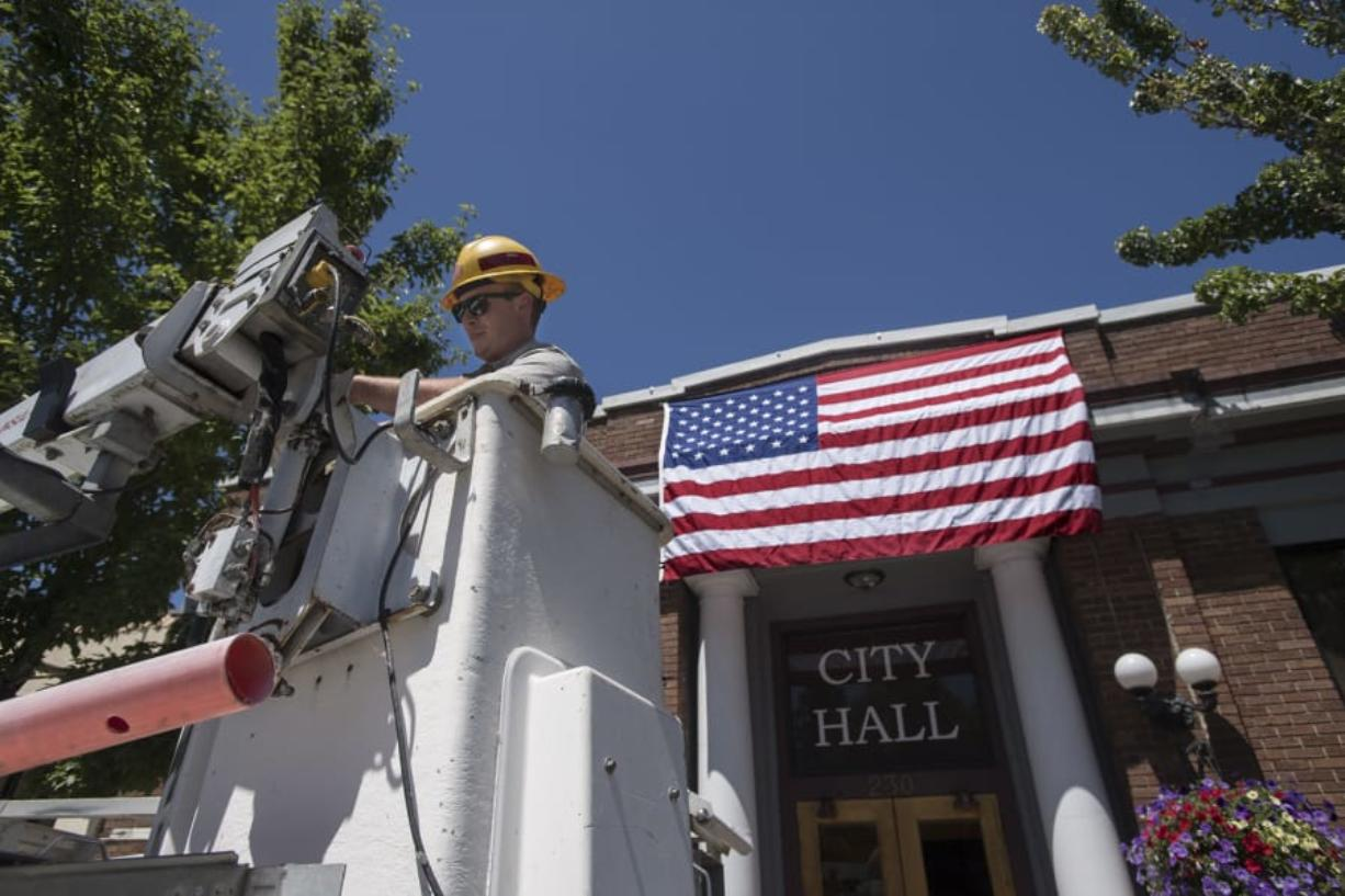 Spencer Kauffman, a facilities maintenance worker with the city of Ridgefield, helps secure the American flag outside City Hall on Tuesday afternoon in preparation for the upcoming Fourth of July parade. Kauffman, who said he planned to help out during the parade, said he was looking forward to the festivities and planned to watch fireworks with loved ones later in the evening. Amanda Cowan/The Columbian