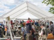 Shoppers at the NW's Largest Garage Sale & Vintage Sale browse under a shaded stall at the Clark County Event Center at the Fairgrounds on Saturday. Organizers said there were 500 vendors there hoping to sell to thousands of shoppers.