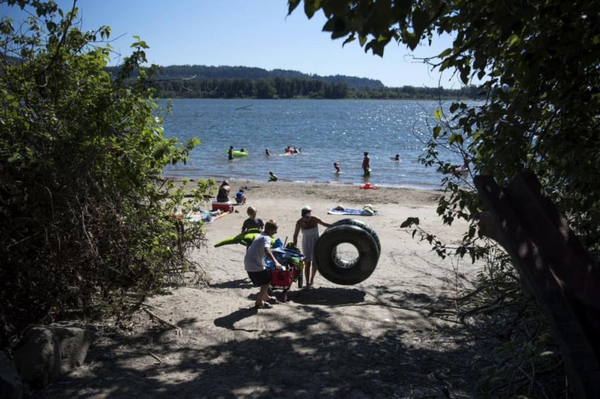 Andrew Helt, 12, left, his brother Patrick, 10, and their mother, Amy Brown, right, all of Washougal, make their way up the path after spending the afternoon at Cottonwood Beach in Washougal on July 11. Brown said the family visited Crown Park pool often in past summers so they've been trying to find new places to swim.
