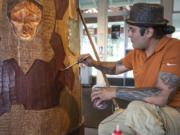Yakama artist Toma Villa does some touch-up work Friday after repairing a crack in the wood in his Spirit Pole sculpture at the Fort Vancouver Visitor Center.