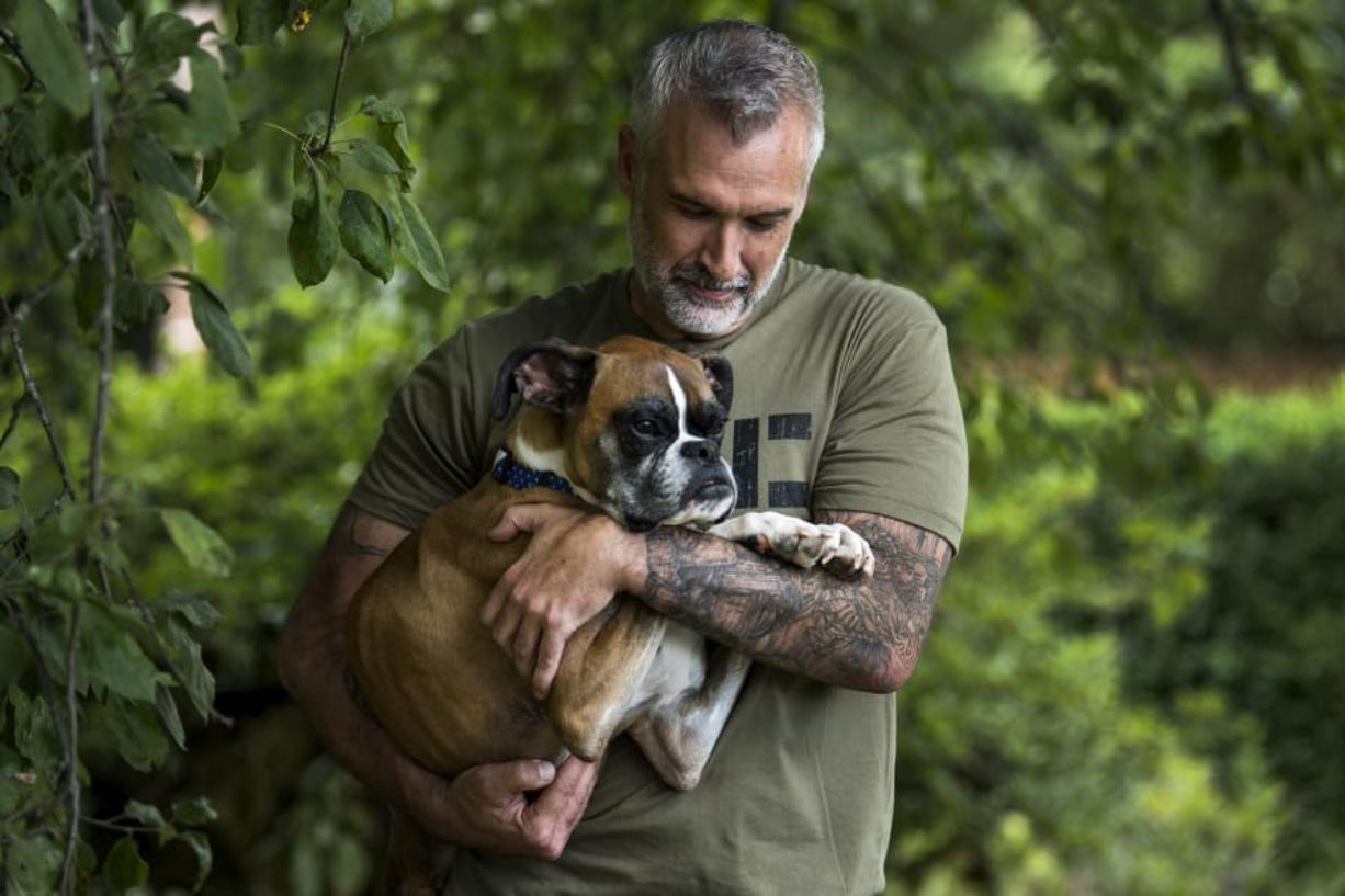 Duncan Lou Who is cradled by one of his owners, Gary Walters, outside Gary and his fiancée Amanda Giese's home in Washougal. Against all odds, Duncan has made it to his fifth birthday, which was July 14.