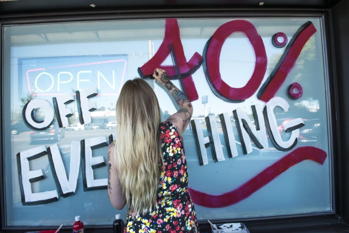 Jessie Leonetti, a budtender at Sticky's Pot Shop, paints a sale announcement on the store's window. The Hazel Dell pot shop will close soon after the state Supreme Court declined to hear their appeal to lift the ban on recreational marijuana sales in unincorporated Clark County. (Nathan Howard/The Columbian)