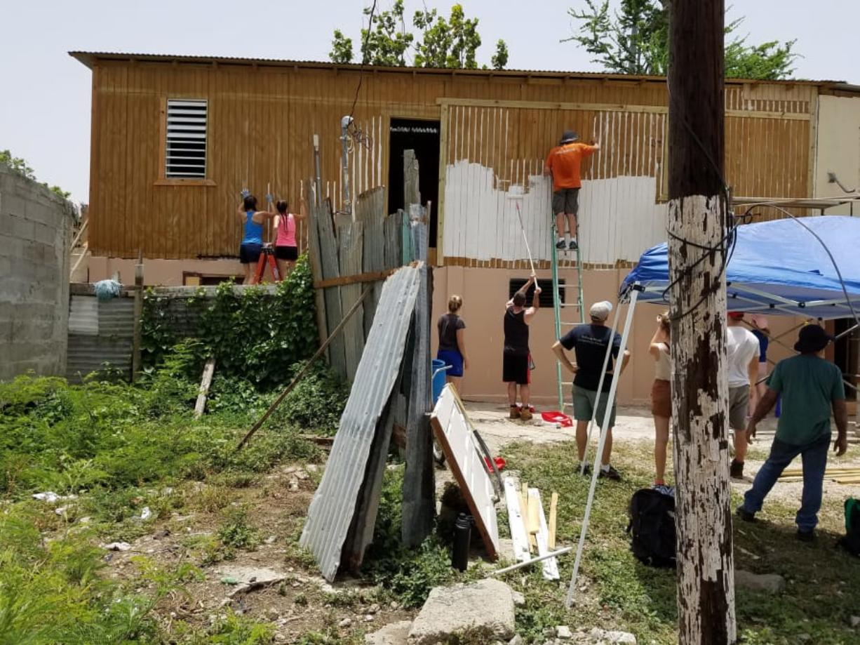 A team of volunteers paints the exterior of a home damaged in Hurricane Maria in Ponce, Puerto Rico. The 26-person group made up a trip organized by Forward Edge International, a Vancouver-based Christian nonprofit.
