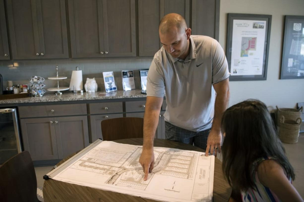 Jeff Wilkins, left, and his daughter, Emily, both of Vancouver, spot their new home at the Four Seasons Lane subdivision, one of Ginn Development's projects in Vancouver. The homes are priced sell for less than Clark County's median home price. Reservations for the first homes are underway.