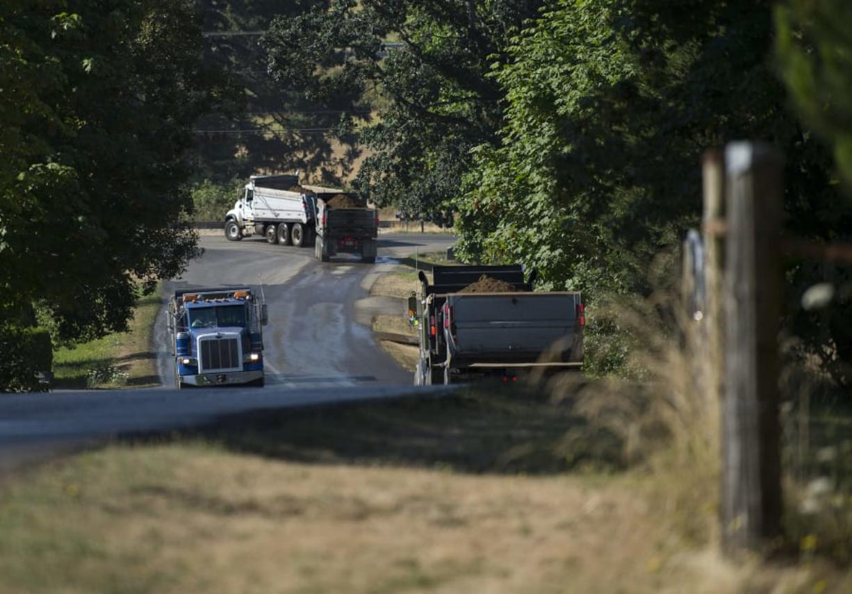 A trio of trucks travel to and from the Zimmerly gravel pit near Washougal. (Amanda Cowan/The Columbian files)