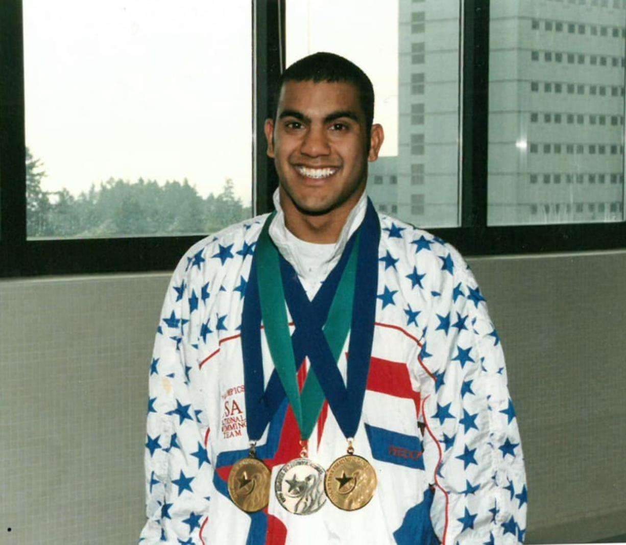 Aaron Paulson poses for a photo at Shriners Hospital holding his medals: two golds and a bronze, which he won for swimming at the 1996 Paralympics in Atlanta, Ga. A patient himself there from age 1 to 21, he makes visits to the hospital to share his story with children. Contributed photo