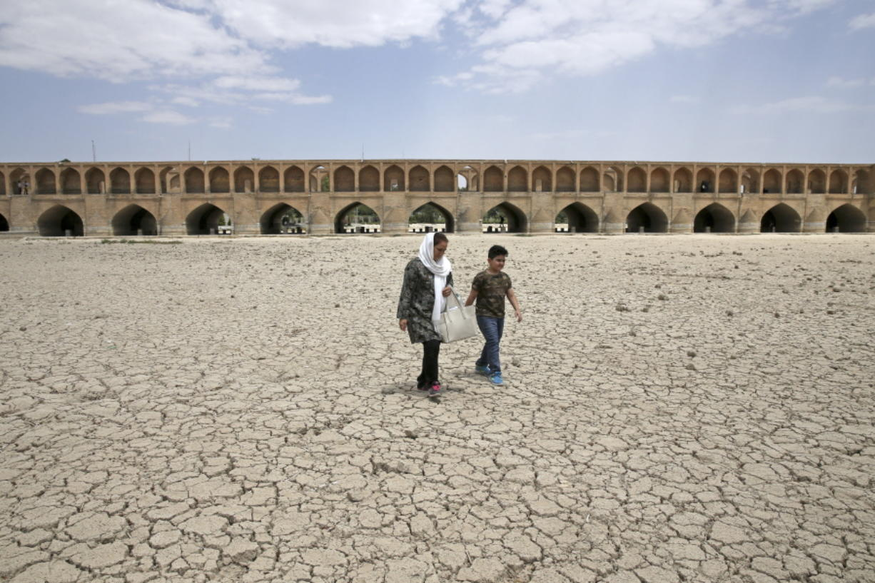 A woman and a boy walk July 10 on the dry riverbed of the Zayandeh Roud river that used to flow under the 400-year-old Si-o-seh Pol bridge in Isfahan, Iran. Farmers in central Iran are increasingly turning to protests, pleading to authorities for a solution as years of drought and government mismanagement of water destroy their livelihoods.