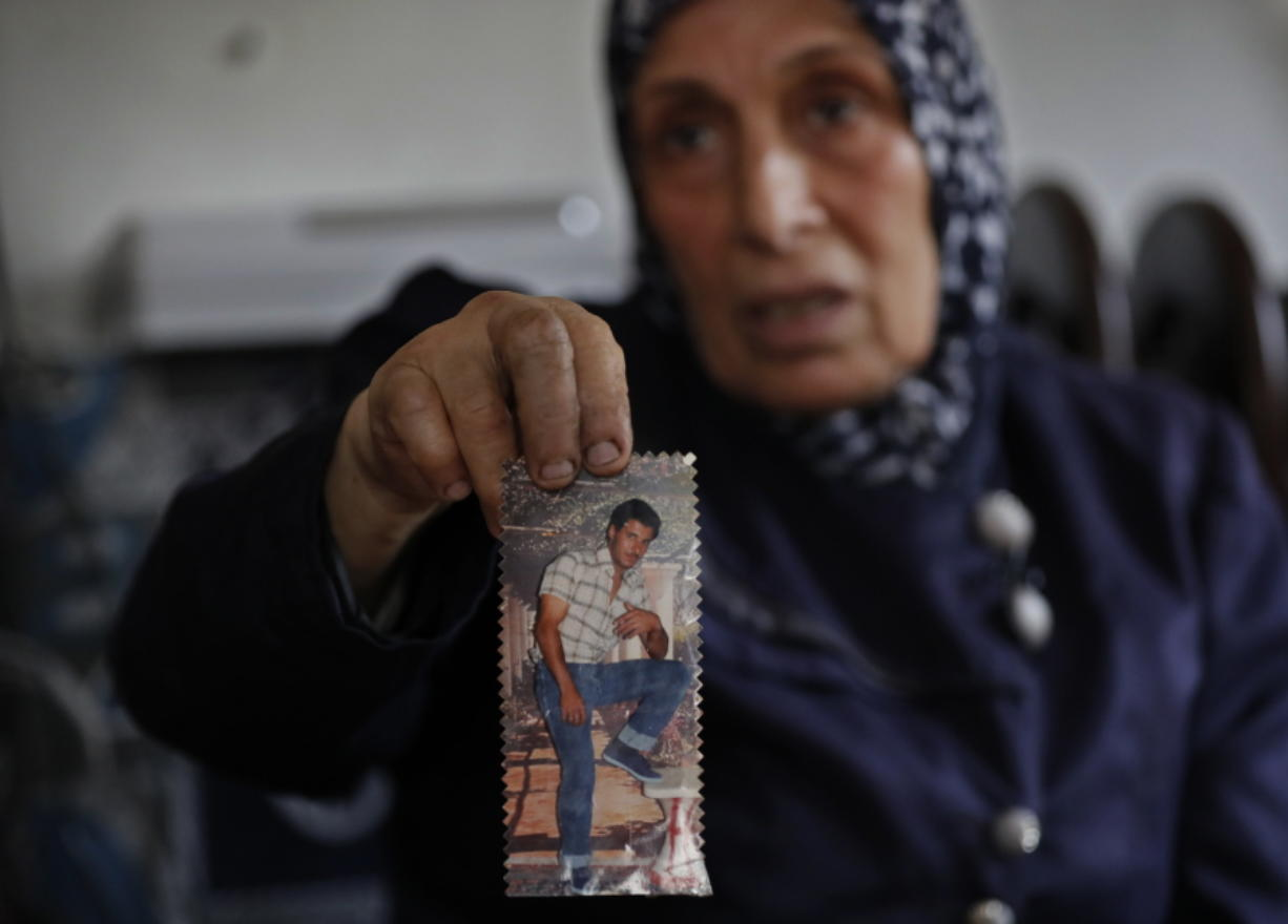 Dahouk al-Omar, 68, an unregistered Syrian refugee woman, shows an old picture of her son Fadi who resettled in U.S, Chicago state, during an interview with The Associated Press, at her house, in Tripoli, north Lebanon. al-Omar hoping she can join her son in Chicago. The Trump administration travel ban has thrown yet another obstacle in the way of Syrian refugees whose status in neighboring countries is already extremely uncertain.