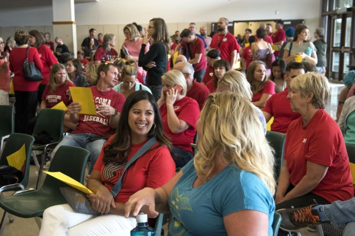 Nicole Chandler, a teacher at Wy'east Middle School, left, and Jennifer Smith, a teacher at Frontier Middle School, right, chat in the overflow cafeteria space before the Evergreen Education Association general membership meeting at Evergreen High School in Vancouver on Thursday. Alisha Jucevic/The Columbian