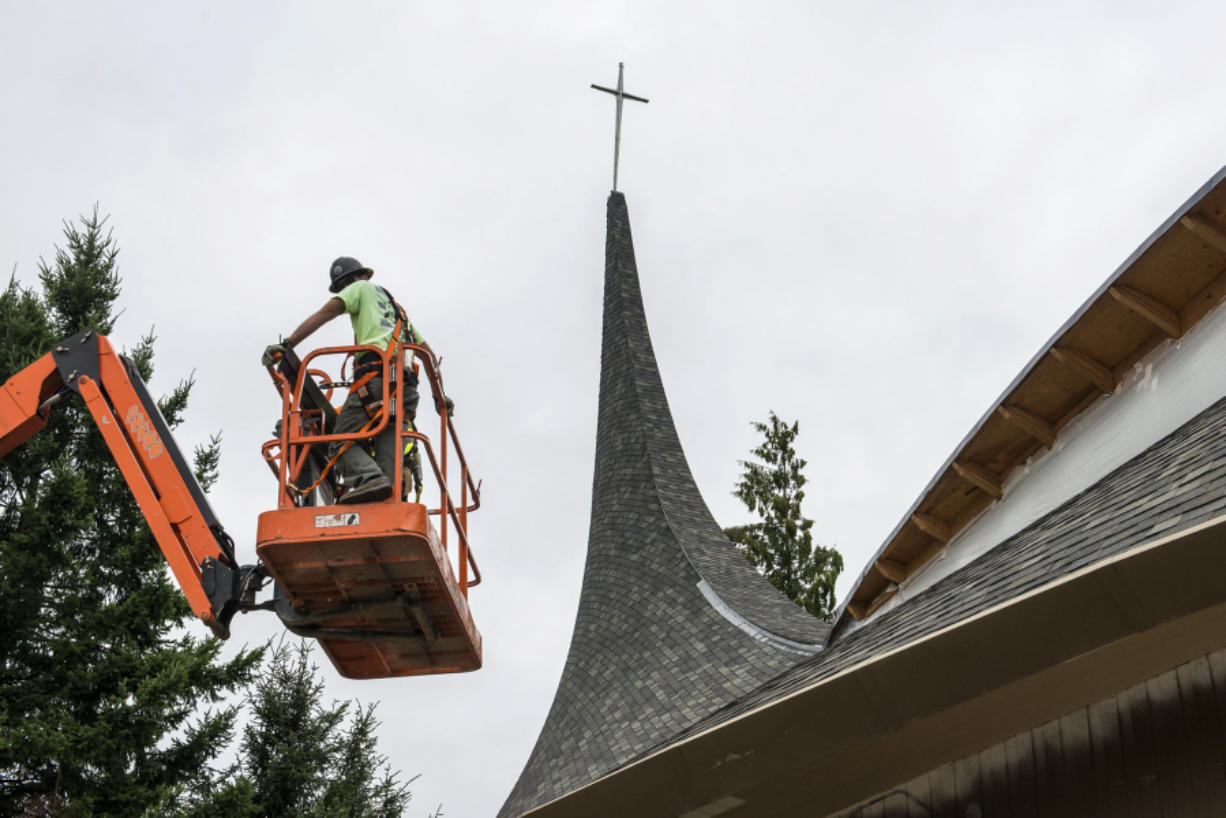 A contractor working at Vancouver United Church of Christ prepares to install new windows on July 19. The church's west steeple was damaged by fire in May 2016.
