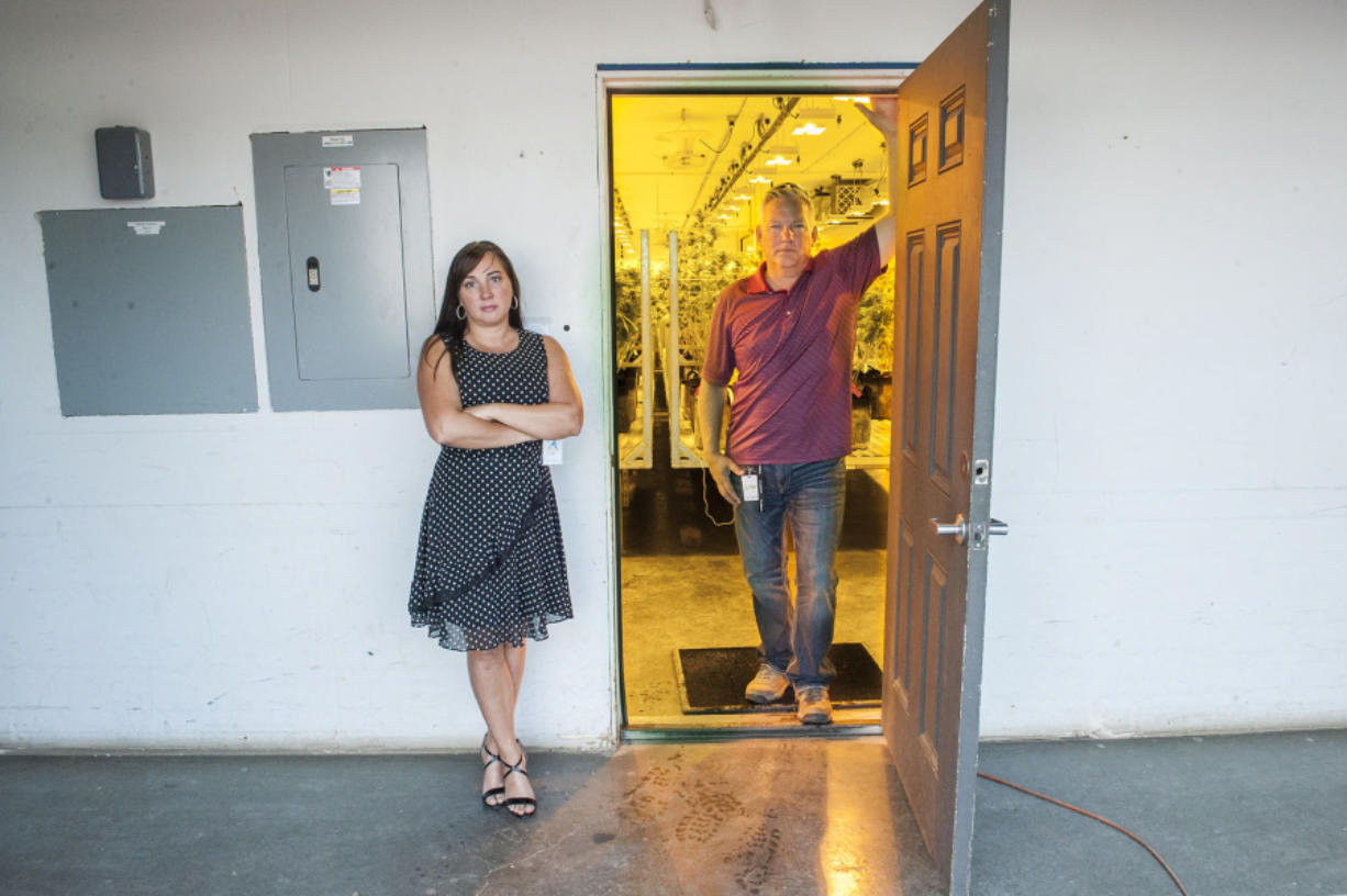 Tracy and Ty Camp pose at the entrance to the grow room at Sunshine Farms. Ty Camp owns the business, but Tracy Camp ultimately lost her banking job as a result.