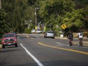 "Luke Youngblood of Camas, left, and Devin Garrett of Washougal, right, make their way down the hill on McLoughlin Boulevard on Friday. ""Going uphill sucks,"" Youngblood said. ""You're out in the middle of the lane."" The city is proposing to make East McLoughlin safer for cyclists and are discussing the possibility of removing on-street parking to build a double bike lane."