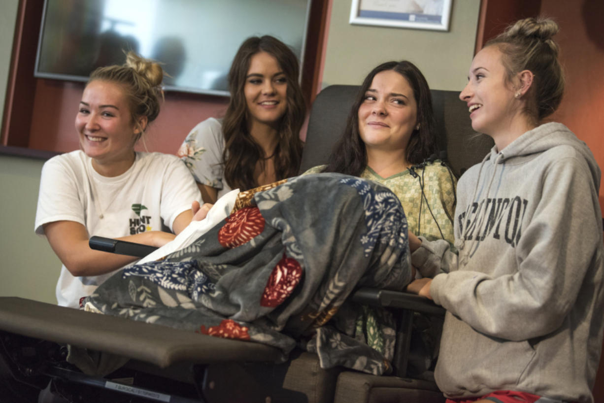 Jordan Holgerson, in chair, is surrounded by friends and family while joking with the media about her injuries at PeaceHealth Southwest Medical. Surrounding Holgerson are, from left, friend Masey Tucker, sister Kaytlin Holgerson and friend Taylor Lavigne.