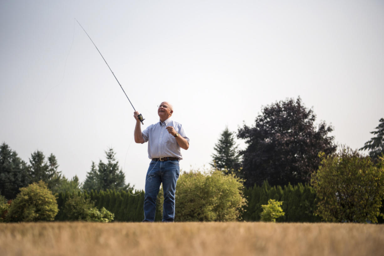 Mike McCoy, owner of Snake Brand Products, demonstrates fly-casting techniques on the lawn outside his workshop. McCoy makes a patented line guide for fly rods that enables fishers to cast farther and more accurately.