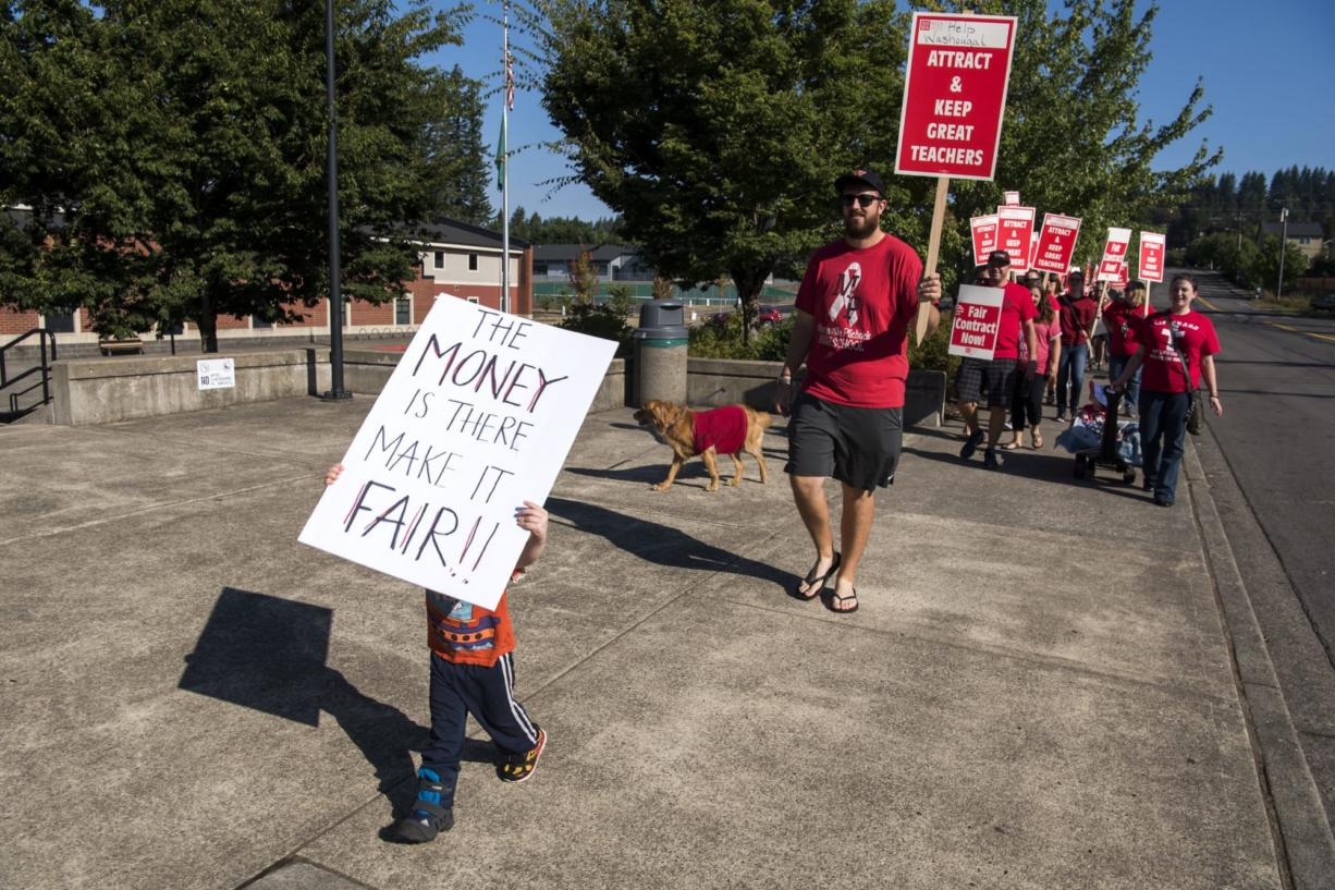 Timothy Tauscher of Washoughal, 3, marches in front of the teachers outside Washougal High School during the first day of the strike on Tuesday, Aug. 28, 2018. Tauscher's grandmother is a teacher at the school so his mother, Ellie, brought him out to help support her and the other teachers.