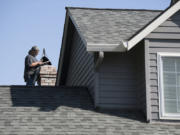 """Dan Dilley, a chimney sweeper and owner of """"A"""" Your Town Chimney, checks a chimney atop a customer's home Tuesday in Camas. He has been sweeping chimneys for more than 30 years and has owned his Washougal business since 1996."""