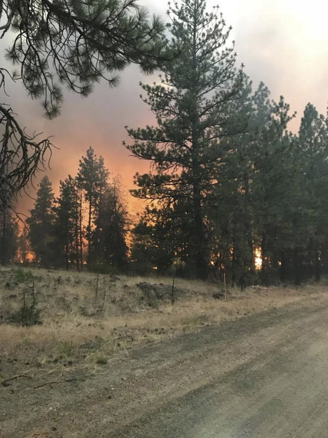 In this photo released by The Eastern Area Incident Management Team, a fire burns along a road as crews continues to battle a wildfire in eastern Washington state Sunday, Aug. 5, 2018.
