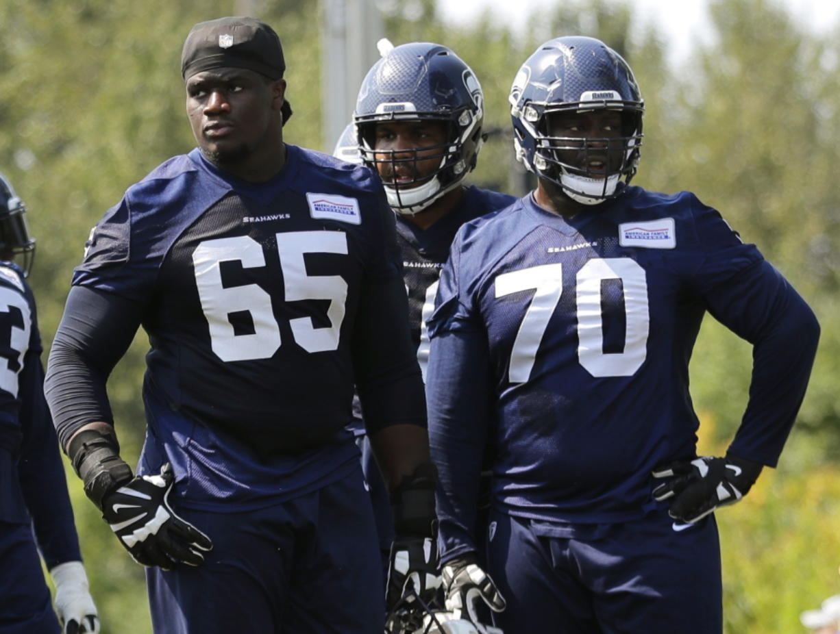 Seattle Seahawks offensive guard Germain Ifedi (65) stands on the field next to offensive guard Rees Odhiambo (70) during NFL football training camp, Monday, Aug. 6, 2018, in Renton, Wash. (AP Photo/Ted S.
