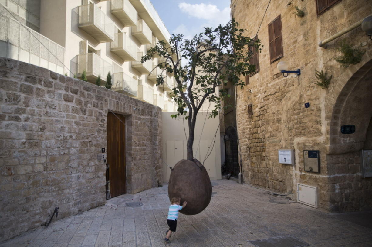In this Saturday, July 28, 2018 photo, a child plays next to a 100-year-old orange tree hanging above the ground in the old city of Jaffa, Israel. Israel's port city of Jaffa is an ancient place. Today glass towers and modern apartment complexes rise amid Jaffa's old white stone buildings. It's famous for its flea market and hummus cafes. But visitors will also find trendy bars, galleries and boutiques. (AP Photo/Oded Balilty)