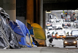 Tarp-covered tents line a sidewalk beneath a highway and adjacent to downtown Seattle on March 8, 20