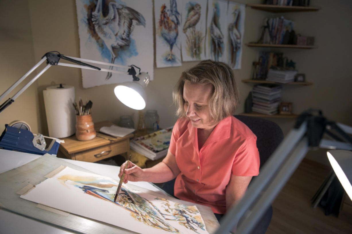 Watercolorist Denise Joy McFadden works on a seabird in her home studio in Cascade Park. She and her husband frequent the Oregon coast to go birding and find subjects for her paintings, she said. Alisha Jucevic/The Columbian