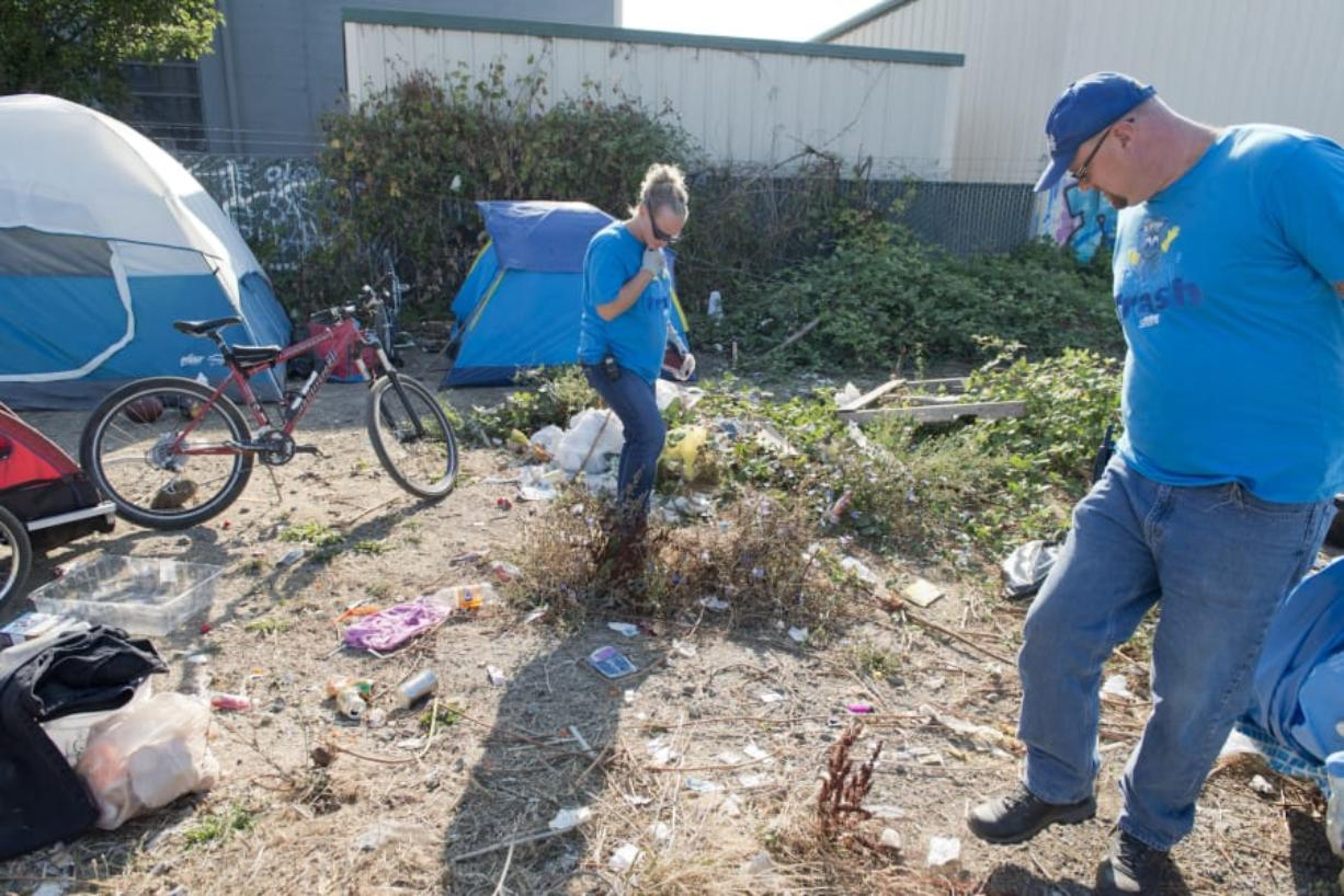 Jennifer Klein and Matt Curry check for needles before cleaning a homeless camp in west Vancouver. The Talkin' Trash program gives jobs to homeless or formerly homeless people and reduces litter around the city.