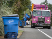 A Waste Connections driver collects curbside recycling bins from a Vancouver neighborhood.