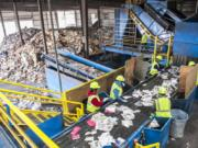Line sorters comb through plastics and paper moving along a conveyor belt at Waste Connections Washington-Clark County material recycling facility on Northwest Lower River Road. The site processes tens of thousands of tons of recyclable materials every year, mostly from Clark County.