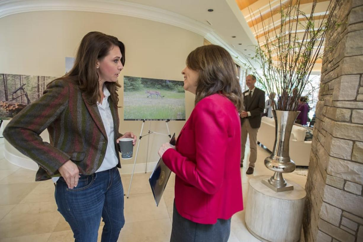 Rep. Jaime Herrera Beutler, R-Battle Ground, left, and Sen. Maria Cantwell, D-Wash., chat Monday morning at the Ed and Dollie Lynch house while celebrating with Columbia Land Trust supporters for their work preserving forests surrounding Mount St. Helens.