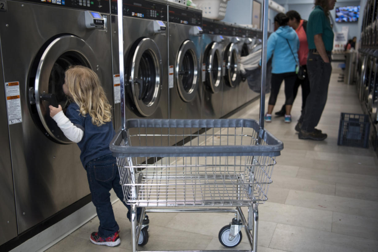 Leo Guerra, 3, peeks in the washer before helping his parents unload laundry at Cedars Laundromat in Woodland on Sept. 11, when the laundromat was hosting its monthly Laundry Love event where people can do laundry for free. The national program was brought to Woodland in April by DeeAnna Holland.