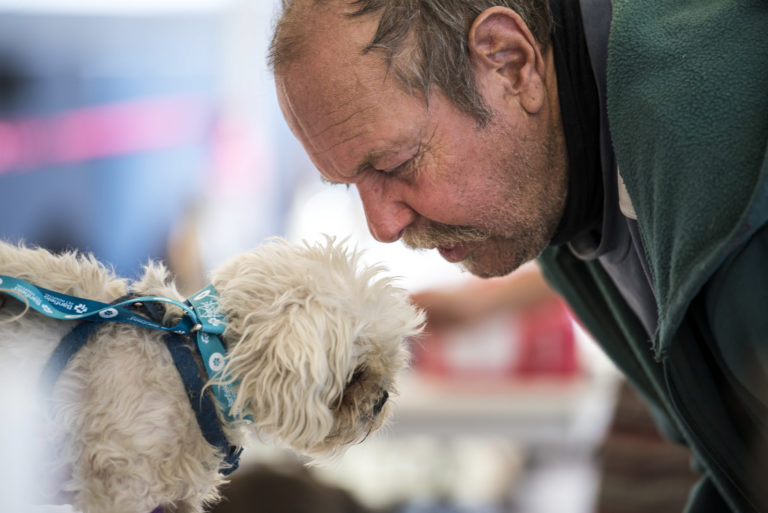 J.C. Ingram of Vancouver leans in to comfort his four-year-old dog Fritzy during the free pet clinic at Open House Ministries on Thursday afternoon, Sept. 20, 2018. (Nathan Howard/The Columbian)