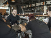 Nick Yahn of Battle Ground, a WildFin American Grill bartender, laughs while practicing menu cocktails with the rest of the bartending staff during training at The Vancouver Waterfront on Thursday morning.