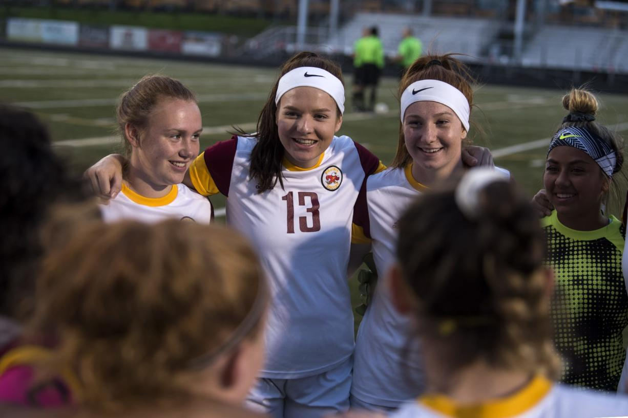 Anna Neal (13) circles up with her Prairie teammates before Tuesday night's game against Camas at Doc Harris Stadium in Camas on Sept. 18, 2018. Camas won 10-3.