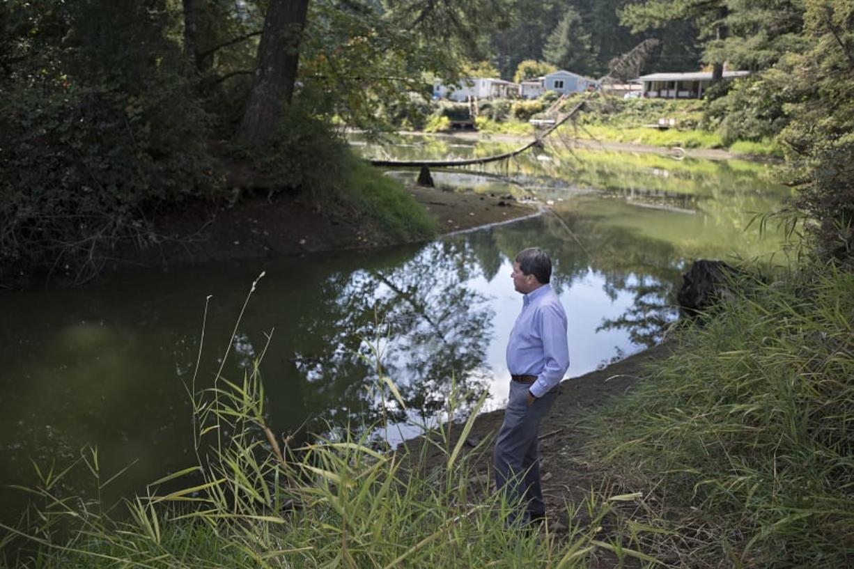 Camas city administrator Pete Capell looks over water that was diverted from Round Lake toward the mill ditch area. Georgia-Pacific recently donated about 181 acres appraised at $960,000 that was owned by the Camas paper mill to the city to be used for green space and recreation. Top: The dam at Lacamas Park, which was recently donated to the city of Camas from Georgia-Pacific, is seen Thursday during the annual partial draining of Round Lake for maintenance work.