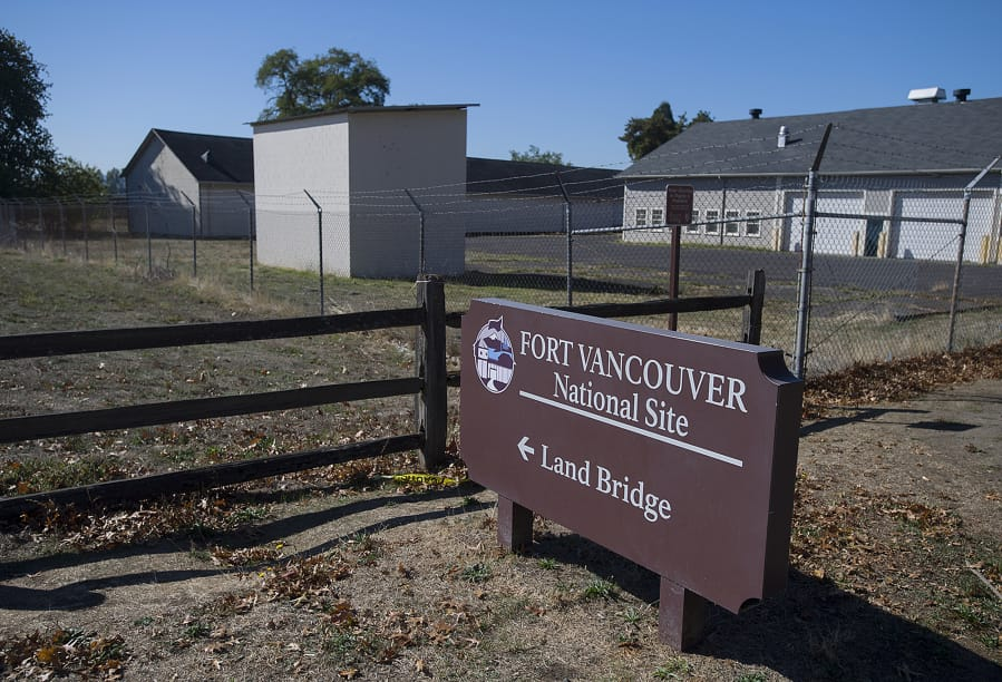 A sign welcomes visitors to Fort Vancouver National Site as a historical warehouse building, skinny