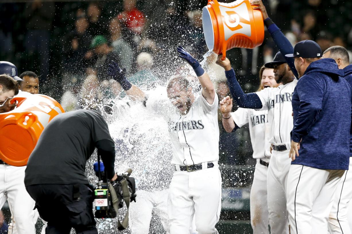 Seattle Mariners' Chris Herrmann gets a Gatorade shower after hitting a walk-off two-run home run against the Oakland Athletics during the eleventh inning of a baseball game Tuesday, Sept. 25, 2018, in Seattle. Seattle won 10-8.