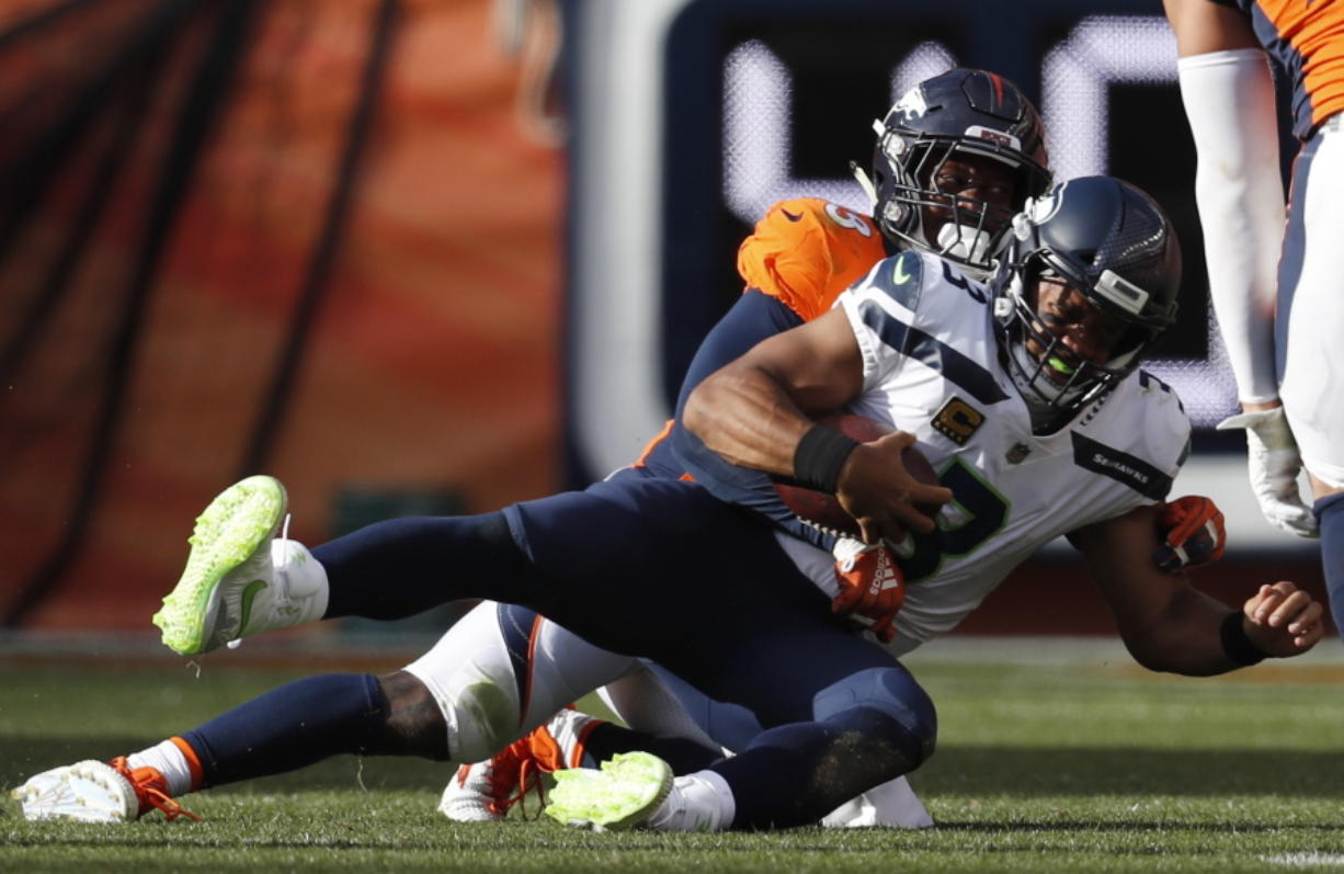 Denver Broncos linebacker Von Miller, behind, hauls down Seattle Seahawks quarterback Russell Wilson (3) for a sack during the second half of an NFL football game Sunday, Sept. 9, 2018, in Denver.