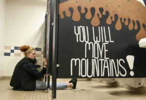 Madison Smith paints a stall in the girls room Tuesday afternoon at Crossroads High School in Granit