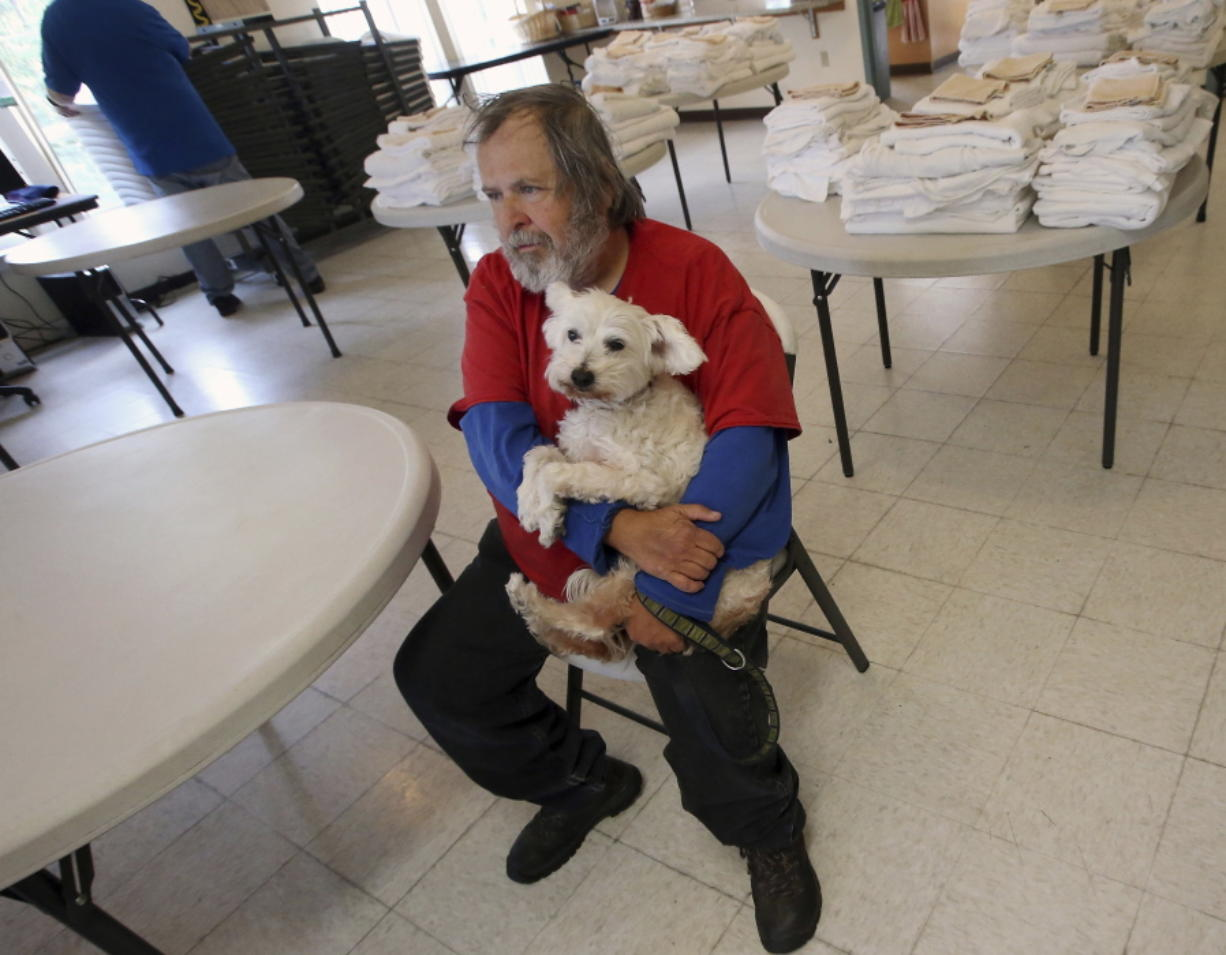 In this photo taken Sept. 20, 2018, Walter Jacque holds his service dog Andy while talking about his respite stay at Benedict House in Bremerton, Wash. (Meegan M.