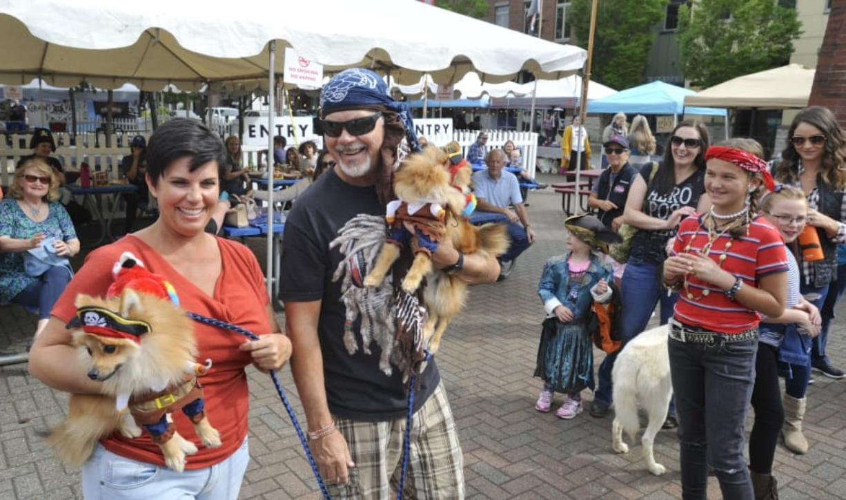 Meshelle Sharples, left, and Raynel Hunt carry Romeo and Raja to collect their parade prize Saturday during Pirates in the Plaza in Washougal.