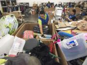 Lucia Mercado, Goodwill production associate, sorts through donations at the Fisher's Landing Goodwill in east Vancouver. In the last year, more than 250 million pounds of household items were donated to Goodwill Industries of the Columbia Willamette. If an item's price is too high, causing it not to sell, it goes to a Goodwill Outlet location.