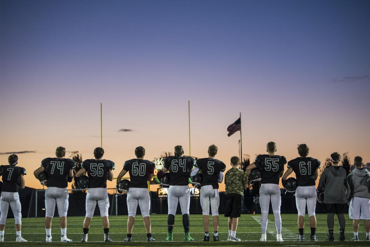 Woodland players listen to the national anthem before their game against Ridgefield at Woodland High School on Friday night, Oct. 12, 2018. (Nathan Howard/The Columbian)
