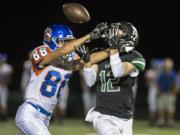 A Ridgefield defender tries and fails to breakup a pass to Woodland's Wyatt Wooden during a game at Woodland High School on Friday night, Oct. 12, 2018.