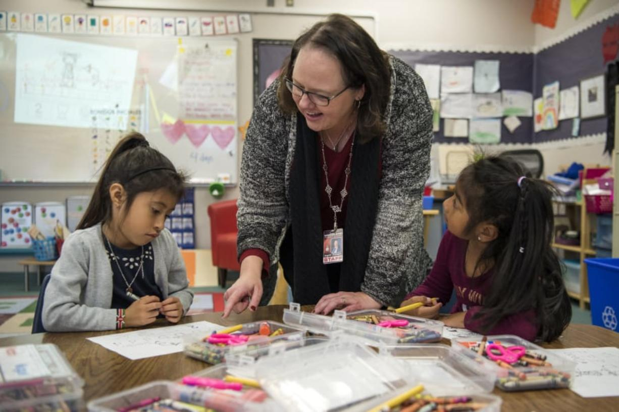 Principal Ingrid Colvard helps Camila Garcia Vasquez, left, and Elisa Martinez Lopez with an alphabet exercise in one of the dual language kindergarten classes at Woodland Primary School. (Alisha Jucevic/The Columbian)
