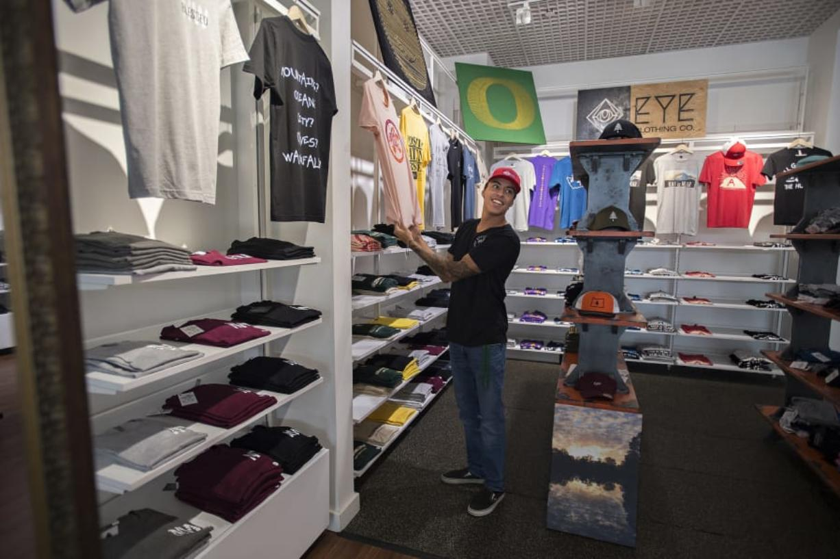 Roberto Gonzalez, owner of EYE Clothing Co., greets customers Thursday while working in Vancouver Mall .