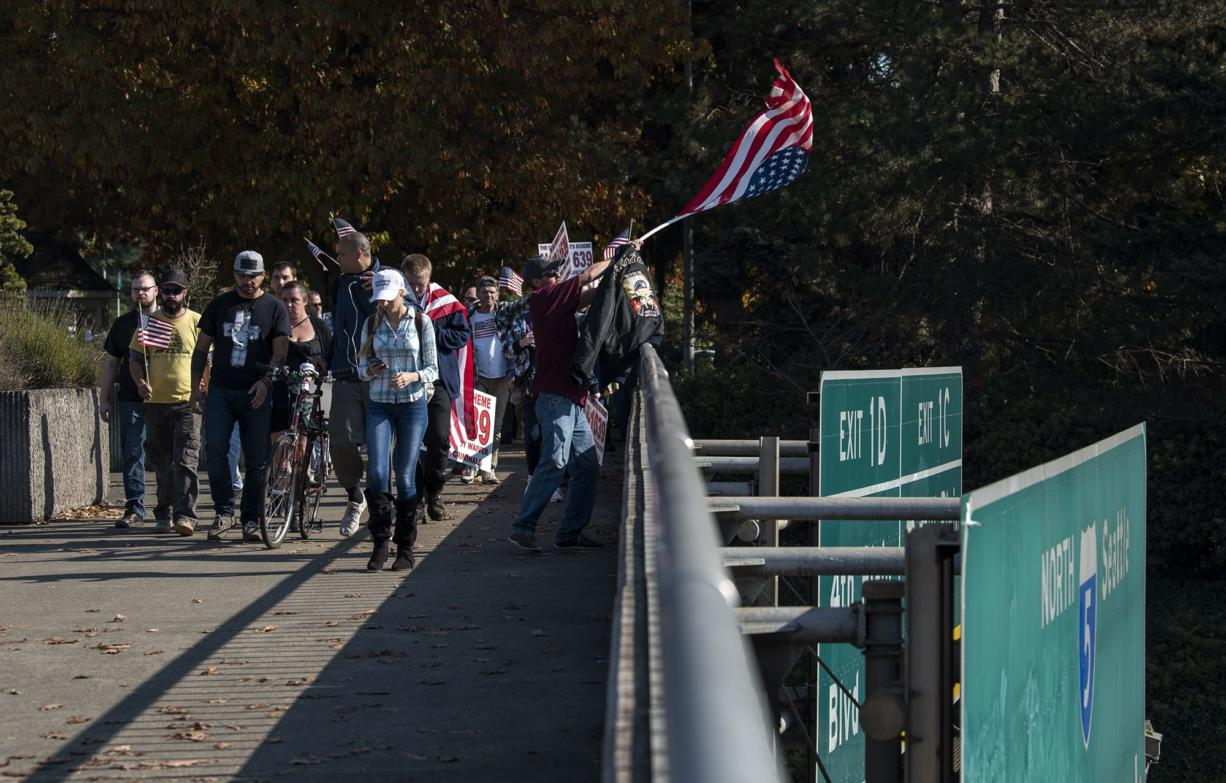 Participants of a rally organized by Patriot Prayer in opposition of Initiative 1639 march down to the East Evergreen Boulevard overpass in Vancouver on Monday afternoon, Oct. 22, 2018.