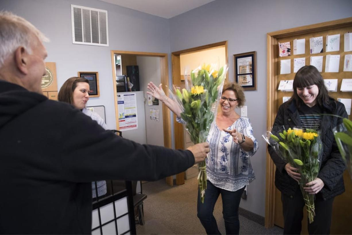 Benno Dobbe, owner of Woodland's Holland America Flower Gardens, from left, hands flowers to Kim Hulett, Lois Hulett and Shari Hartshorn of Woodland Insurance Agency during Wednesday's Petal It Forward. Holland America was one of more than 450 participants in the nationwide event, where florists go out and give away free flowers.
