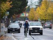 A cyclist navigates through traffic on Columbia Street near the intersection with West Sixth Street, while at left in the background a car blocks the bike lane. Via the Westside Bike Mobility Project, the city is designing north-south bike routes to enable riders of varying abilities to ride between downtown Vancouver and the city's other west-side neighborhoods.